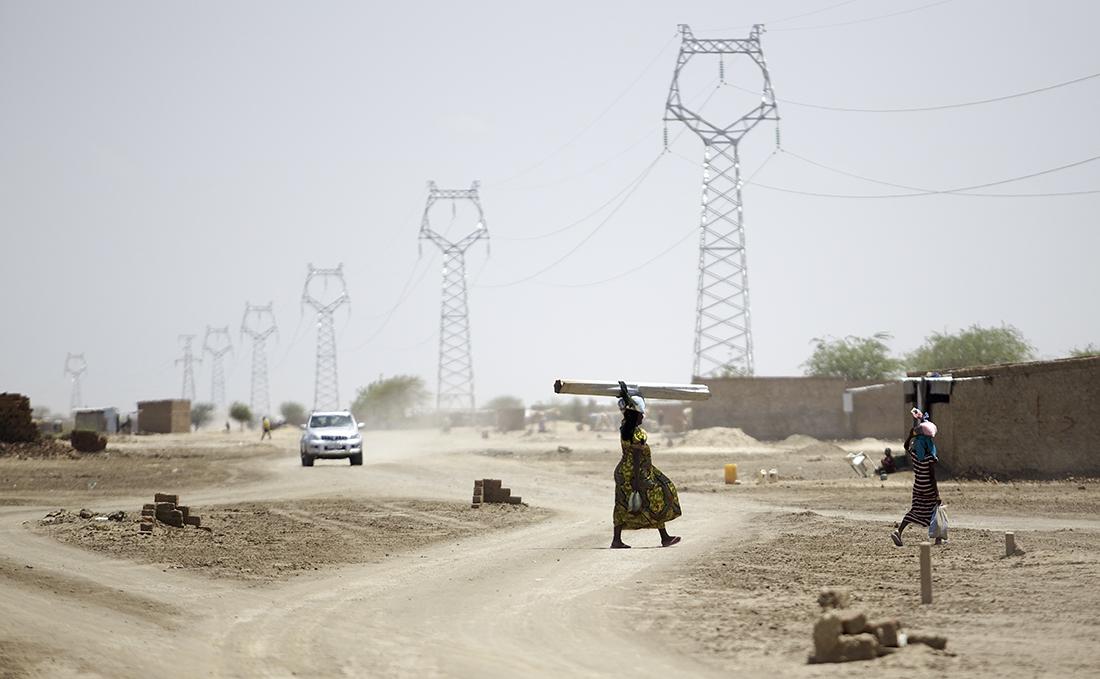 Dos mujeres cruzan un camino delante de un tendido eléctrico cerca de Yamena, la capital del país / Getty Images