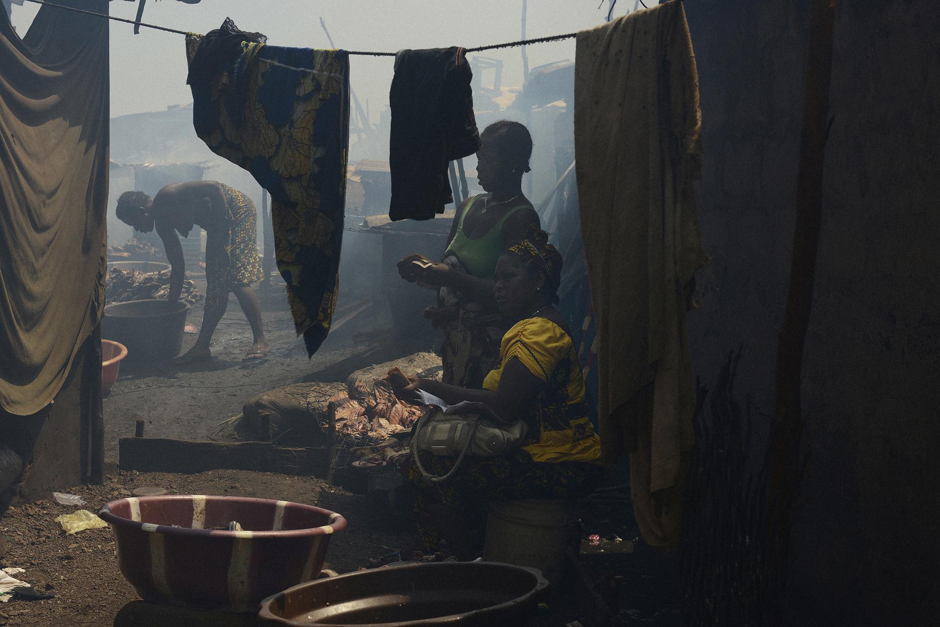 Sierra Leone. Freetown. La capital es una ciudad altamente poblada. La densidad de población y los suburbios ayudaron en la propagación del virus del ébola. También contribuyó la falta de higiene y las tradiciones y constumbres ancestrales y religiosas, como la de lavar y tocar efusivamente a sus muertos. Precisamente en los cadáveres es donde más activo y virulento es el ébola. En la imagen unas mujeres comercian con carne en el suburbio de pescadores de Moa Wharf que fue el epicentro del ébola en la ciudad.