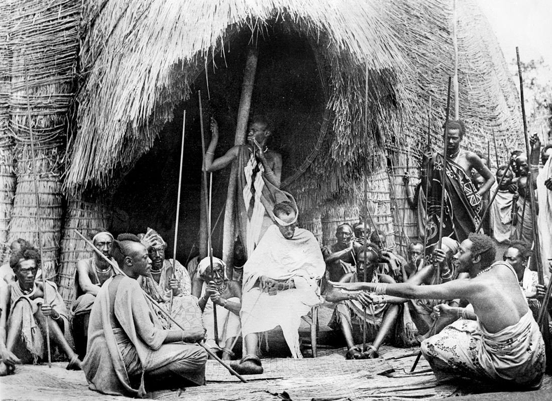 El rey Musinga en una reunión del consejo de jefes comunitarios celebrada en la entrada de la choza real. Musinga fue el último monarca que vivió en la choza / Fotografía: Getty Images