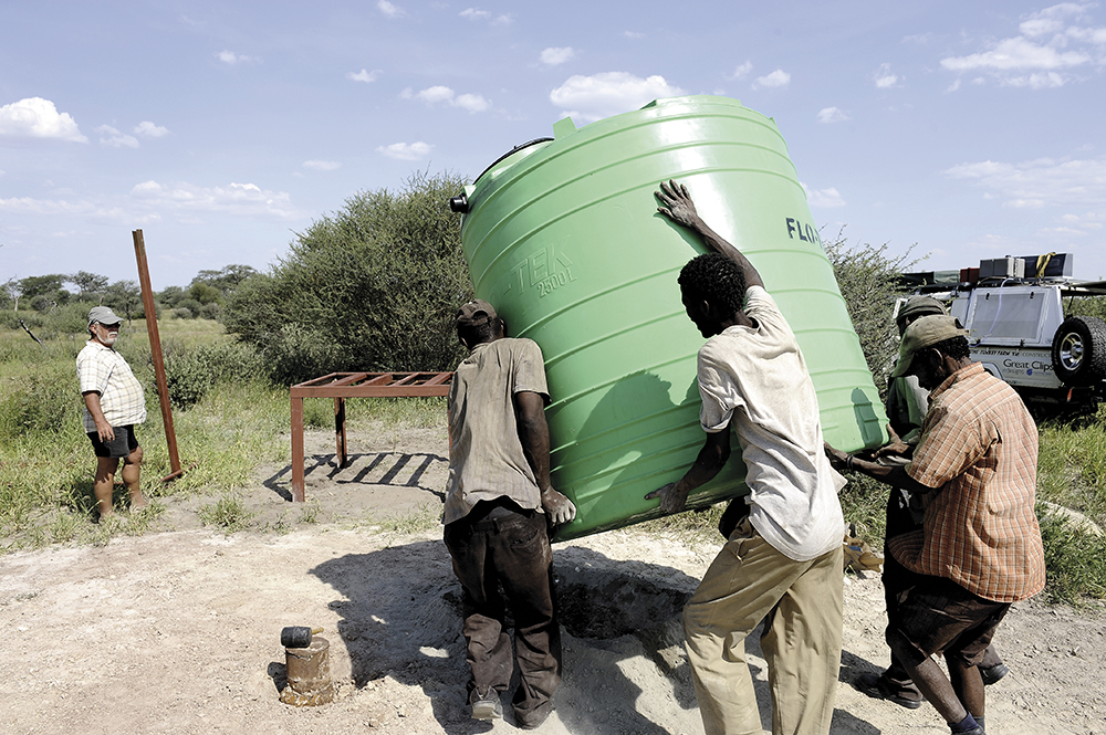Varios bosquimanos portan un depósito de agua en el centro de la reserva del Kalahari, el 19 de febrero de 2012 / Fotografía: Getty Images